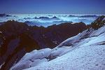 Gipfelblick in die Nordflanke mit Aufstiegsspur und Meer der Berge im Osten
