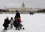 Kinder und Mütter mit Kinderwagen auf dem zugefroreren See mit Schnee bedeckt, Hintergrund Schloss Charlottenburg. Foto: Helga Karl
