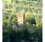 Strommasten und Stromleitungen vor einer Burgruine auf einem Felsen. Foto: Helga Karl