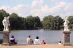 Sommer-Sonne im Schlosspark. Menschen sitzen auf den Stufen zum See mit Blick auf die Rote Brücke. Foto: Helga Karl