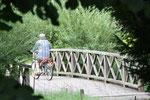 Radfahrer auf Holzbrücke. Schlosspark Charlottenburg. Foto © Helga Karl
