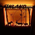 décoration en bois, cadre représentant des cervidés et divers animaux de la forêt, avec le nom Finland, le tout illuminé la nuit