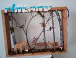 décoration en bois naturelle d'un cadre, représentant des cervidés et divers animaux de la forêt, avec le nom Finland collé en haut du cadre et peint des couleurs du drapeau finlandais