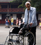 Chinese local pushing his own wheelchair