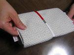 2 中包がすっぽり入ったら、 薄紙の切込部分でタオルと中包を強く指でつまみます。