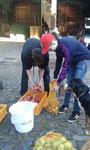 Sabrina und Joshua packen die sauberen Äpfel wieder in Säcke