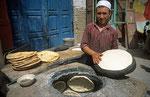 Backen von Fladebrot im Tandori-Ofen, Kashgar, Provinz Xinjiang, VR China