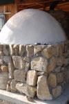 石窯の後ろ姿です。地元の石で土台を組みました。正面は室内に空いています。こうして室内のスペースを有効に使います。