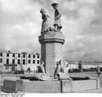 Der heile Brunnen vor dem zerstörten Rathaus nach dem Krieg.
