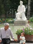 un jeune et son grand'père au pied de la statue de Ferdowsi