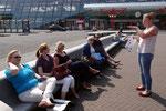 Susanne Rengers erklärt Sehenwürdigkeiten auf dem Bahnhofsvorplatz von Lelystad. Foto: Ulrichs