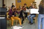 Schüler üben mit zwei Studentinnen ein Musikstück ein.