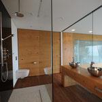 Blick ins Bad mit bodenebener, begehbarer Dusche, Aufsatzwaschbecken, Wandschrank. Kunstdruck auf Glas in der Dusche.