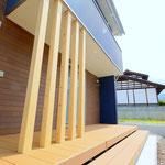 鉄板サイディングと大きなウッドデッキのある外観