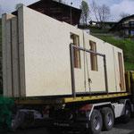 Holzelemente werden auf die Baustelle transportiert.