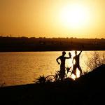 Glückliche Männer nach dem erfrischenden Bad - die verhüllte Frau erfreut sich an den Posen im Sonnenuntergang