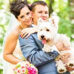 Happy bruidskoppel samen met hun hondje op de trouwfoto