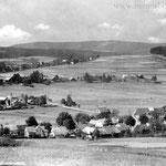 """Blick über Wassersuppen und Roidlmühle auf Neubäu und Mauthaus. Rechts oberhalb des Kamins sieht man die Neubäuer Kapelle. Am Bildrand die Häuser von """"Neu-Neubäu"""" oder Trutschlariad."""