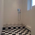 Fugenloses Bad an der Wand vom Stuckateur und Fliesenboden Schachbrett