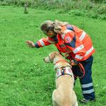 Die Hundeführerin gibt auch hier per Handzeichen die Richtung vor - nach einem Kommandowort läuft der Hund dann los.
