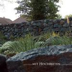 Piesberger Natursteinmauer Hochbeet zur Hofseite bepflanzt mit Gräsern und Stauden 1