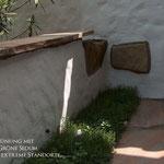 Mediterrane Putzmauer als Sitzmauer mit Natursteinabdeckung