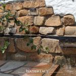 Wasserlauf an mediterraner Putzmauer mit Sandstein