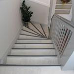 Treppenhausgestaltung mit Laminatverlegung im Boden- und Stufenbereich, Glasgewebe an den Wandflächen und dekorativen Zierprofilen.