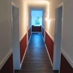 Flurgestaltung mit Holzoptik Bodenbelag, Modellierputz im Sockelbereich, Streichputz im oberen Wandbereich und Zierprofilen an den Wand- und Deckenflächen.