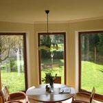 Mineralischer Modellierputz, Zierprofile und abgesetzte Fensterleibungen in einem Wohnzimmer.