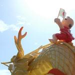 龍の規則正しく流れる鱗と 希望へ向かい旗を掲げる子供