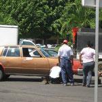 Un auto, averiado, obstruyendo la circulación mientras lo intentan reparar