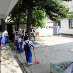 Schüler putzen den Innenhof unseres Dormitorys
