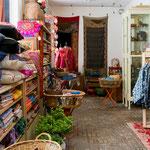 Tissus au mètre, housses de coussin, objets et kalamkari sur le mur du fond...