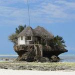 The Rock: eine Gastwirtschaft auf einer sehr strandnahen Insel im Indischen Ozean bei Ebbe.