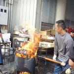 藁火でカツオをあぶってタタキを作っている