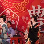 二人の芸者がお座敷遊びの「箸拳」を披露。それぞれ3本ずつの箸を手に持つ。