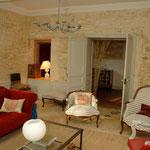 Après : salon triple traversant, chaleur du rouge, confort du velours, tapisserie claire sur mobilier ancien