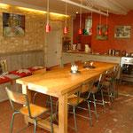 Après :cuisine rénovée dans maison très ancienne : les éléments de décoration sont le lèche mur sur pierres, le béton ciré rouge orangé sur murs, le bois de la table, les chaises d'école et le sol en tomette à l'ancienne.