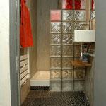 Après : la douche à remplacé la baignoire sabot. Un mur avec pavés de verre créé le pare douche. L'harmonie de rouge sur fond gris donne du peps à cet espace douche.