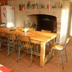 Après : espace repas central avec chaises de laboratoire de récupération, mise en valeur cheminée en pierre, murs en béton cirés et tomettes anciennes au sol