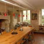 la table repas est au centre de l'espace cuisine, il sert de plan de travail pour la préparation des repas. Le complément technique est le long du mur opposé aux fenêtres