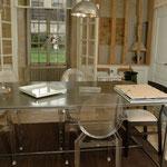 Après : salle à manger traversante avec de multiples accès de la lumière naturelle, une table métallique sur mesure et les chaises transparentes Starck