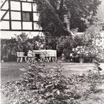 Sitzplatz im Garten - ein Mühlstein dient als Tischplatte