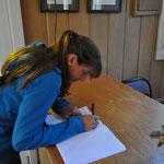 Angi macht einen Eintrag im Gästebuch der Kapelle.
