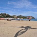 Der Strand in Sayulita - es reiht sich Sonnenschirm an Sonnenschirm. Etliche Surfbeginner sind nebeneinander im Wasser und versuchen die Wellen zu erwischen.