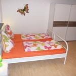 Ferienwohnung Butterfly - Seitenansicht Doppelbett mit Schiebetürenschrank