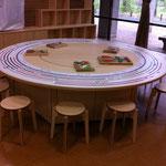 ライブラリーコーナーの円形テーブルだが、天板を外すと、下部が台形の6つの台でできており、いろいろなレイアウトが可能。