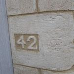 Numéro de rue sculpté dans l'enduit imitation pierre de taille