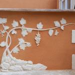 Sculpture d'une vigne avec ses feuilles et ses grappes de raisin, logée dans les pierres